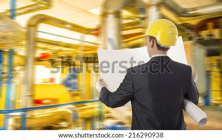 Back view Man working in oil or gas refinery, turning on and off pipeline valve torso and hand engineer yellow holding paper plan, helmet for worker security construction worker Unrecognizable person  - stock photo