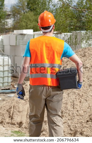 Back view of a blue-collar worker with toolbox and grout float - stock photo