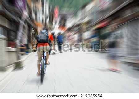 Back view of a blurred tourist cyclist on street in city. - stock photo