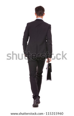 back view of a business man holding a briefcase and walking forward onwhite background - stock photo