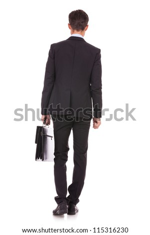back view of a business man standing and holding a briefcase , looking away - stock photo