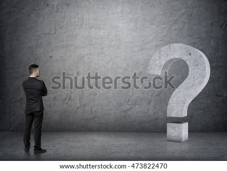 Back view of a businessman looking at big 3D concrete question mark. Ideas and concepts. Business staff. Solving problems. Confusion and uncertainty.