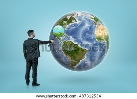 Back view of a businessman looking through magnifying glass on the Earth and seeing grass and green plant. Eco-friendly living. Environment and ecology. Elements of this image are furnished by NASA