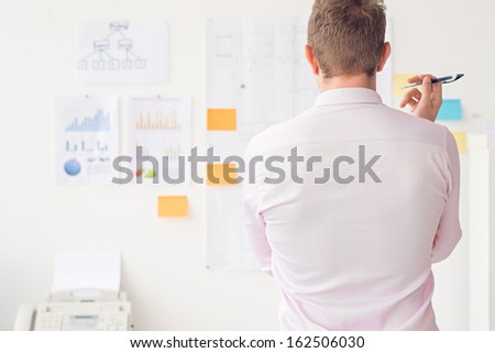 Back view of a businessman standing and contemplating at the office - stock photo