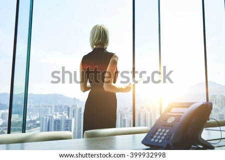 Back view of a businesswoman with digital tablet in hands is watching in office window on a New York city view and thinking about future her company. Female manager is using touch pad during work day - stock photo