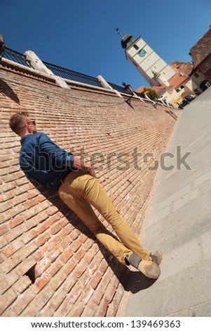 back view of a casual young man standing with hands in pockets by a brick wall and looking at the Council Tower from Sibiu city, Romania