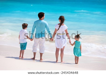 Back view of a Caucasian family at tropical beach - stock photo