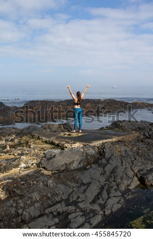 Back-view of a caucasian female in yoga clothes stretching on the rocks of the beach with copyspace - stock photo