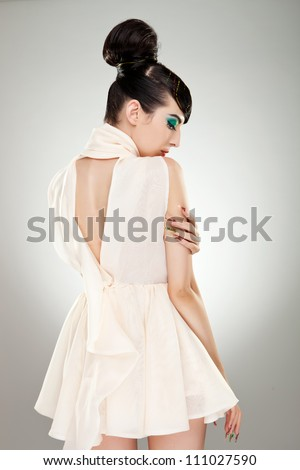 Back view of a charming young woman holding one of her palms on the opposite arm - stock photo