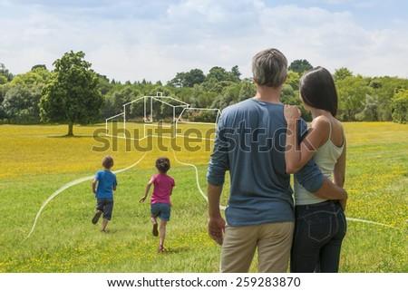 back view of a couple contemplating a landscape while imagining their future home, we see a drawing of the house on the countryside, their  two children that are running towards their dream house - stock photo