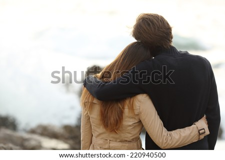 Back view of a couple cuddling in winter isolated in white above - stock photo
