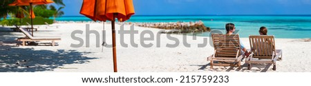 Back view of a couple relaxing on a tropical beach during summer vacation, panorama perfect for banners