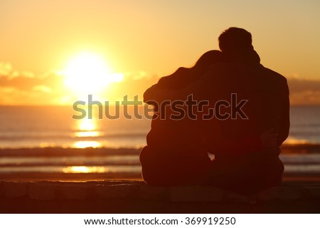 Back view of a couple silhouette watching sun at sunset on the beach in winter with a warmth light - stock photo