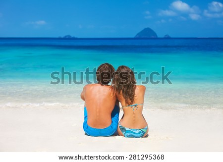 Back view of a couple sitting on the tropical beach during summer vacation  - stock photo