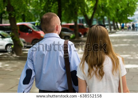 Back view of a couple walking down the street