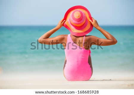 Back view of a cute little girl in pink hat at tropical beach - stock photo