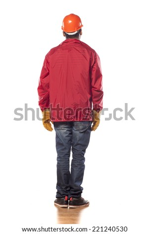 back view of a dark-skinned worker with helmet and gloves - stock photo