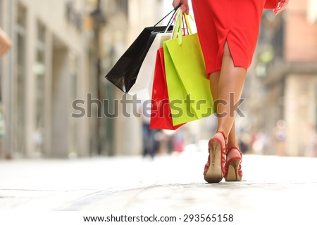 Back view of a fashion shopper woman legs walking with colorful shopping bags in the street - stock photo