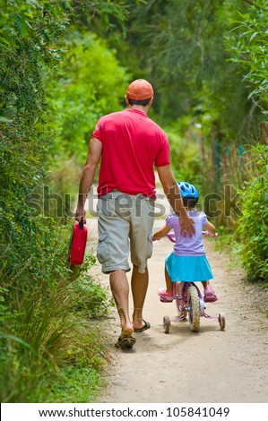 Back view of a father pushing his daughter on a bicycle on a summer day