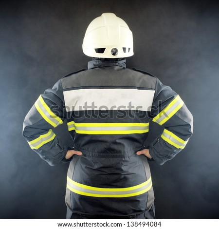 Back view of a fireman in protective suit wearing helmet - stock photo