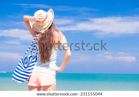 back view of a fit young woman with stripy bag at tropical beach - stock photo