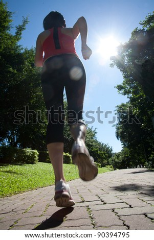 Back view of a girl running against blue background in the park - stock photo