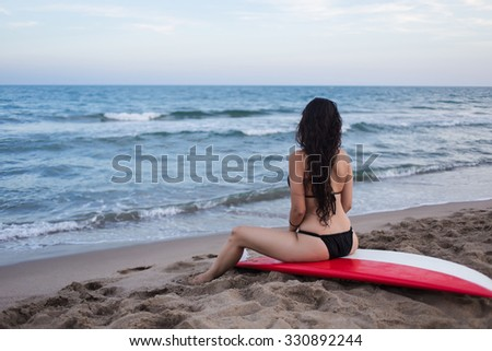 Back view of a girl with slender figure in a bikini sex which emphasizes her beautiful body, young Hispanic woman sitting on surfboard and watching blustering ocean while  enjoying vacation holidays - stock photo