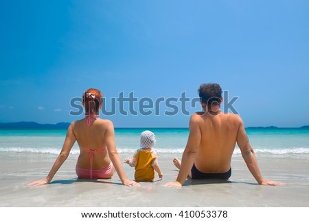 Back view of a happy family on a tropical beach.Mother, father and daughter having fun on tropical white beach. - stock photo