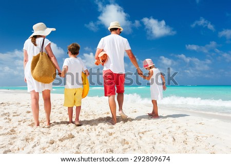 Back view of a happy family with kids on tropical beach vacation - stock photo