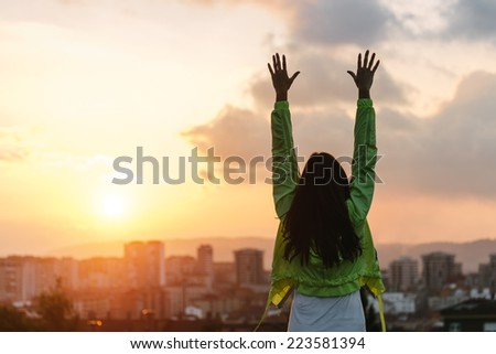 Back view of a happy woman celebrating sport goals and fitness lifestyle success. Female athlete raising arms to the sky after exercising towards beautiful sunset or morning over city skyline. - stock photo