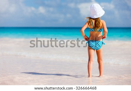 Back view of a little girl at beach during summer vacation - stock photo