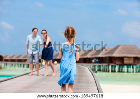 Back view of a little girl running toward her family on wooden jetty at resort - stock photo