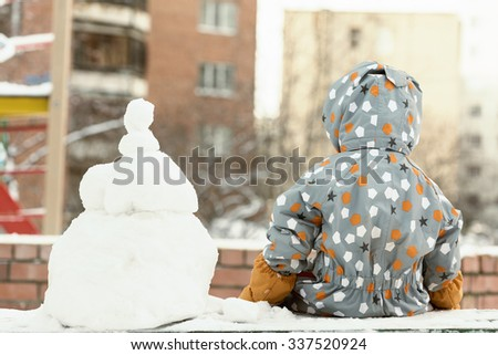 Back view of a little toddler child having rest making a snowman in winter. - stock photo