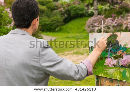 Back view of a male artist with his sketchbook in the park  working  on a trestle and easel painting with oils and acrylics during an art class - stock photo