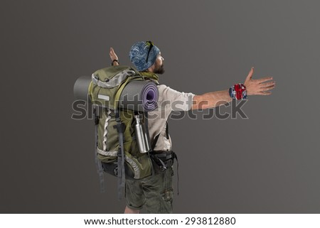back view of a male fully equipped tourist with backpack and the camera on gray background. tourist opened his arms, inviting travel - stock photo