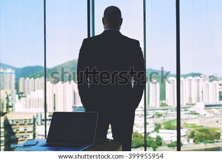Back view of a man confident entrepreneur is looking in big office window, while is waiting when come partner and behind him standing open laptop computer with empty copy space screen for your content - stock photo