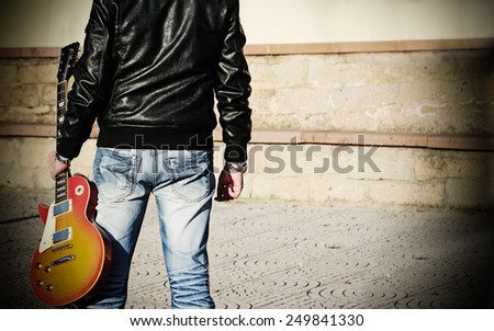 back view of a man holding a guitar  - stock photo