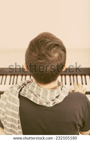 Back view of a man playing piano.