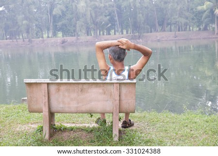 Back view of a man sitting close to a lake  - stock photo