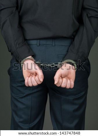 back view of a person dressed in black, hancuffed with their hands behind their back and their palms closed - stock photo