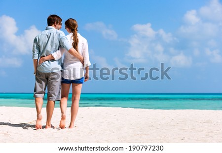Back view of a romantic couple walking at beach during tropical vacation - stock photo