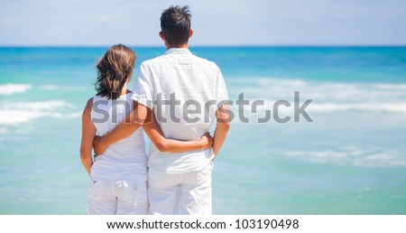 Back view of a romantic happy young couple together on the beach