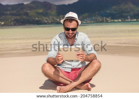 back view of a sexy blonde woman with hat walking towards her love of her life on a paradise beach in the seychelles, with hands in the air and making the victory peace hands sign - stock photo