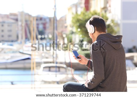 Back view of a teenager listening music with headphones from a smart phone on a vacations destination - stock photo