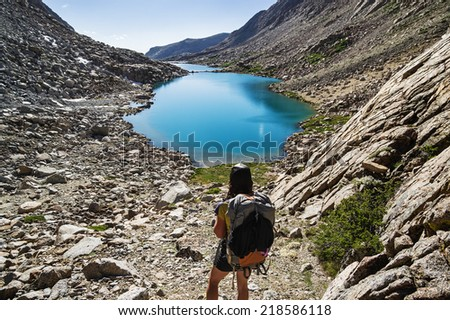 back view of a woman backpacker looking down at glacial lakes in the Darwin Canyon of Kings Canyon National Park - stock photo