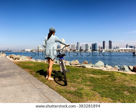 Back view of a woman, holding bicycle, will looking at the bay of San Diego in Southern California.  - stock photo