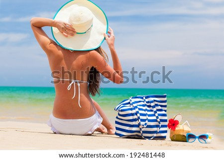 back view of a woman in bikini and straw hat with beach bag and coconut cocktail - stock photo