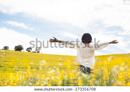 Back view of a woman in yellow field