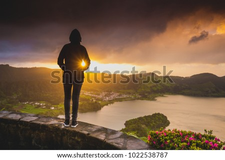 Back view of a woman looking to a beautiful sunset