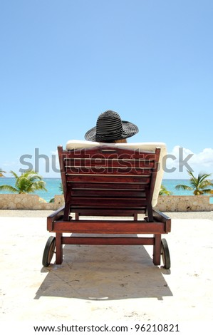 back view of a woman on a long chair in a tropical resort